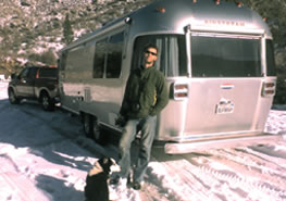 Graham and Flower in front of airstream trailer in snow